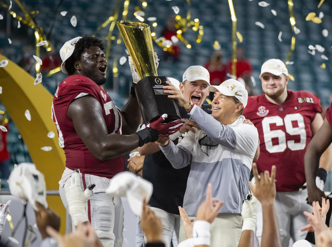 Jan 11, 2021; Miami Gardens, Florida, USA; Alabama Crimson Tide head coach Nick Saban and offensive lineman Alex Leatherwood (70) celebrates with the CFP National Championship trophy after beating the Ohio State Buckeyes in the 2021 College Football Playoff National Championship Game. Mandatory Credit: Mark J. Rebilas-USA TODAY Sports