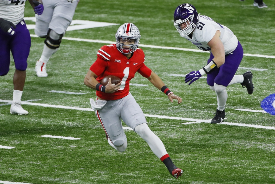 Ohio State Buckeyes quarterback Justin Fields (1) rushes upfield ahead of Northwestern Wildcats linebacker Blake Gallagher (51) during the first quarter of the Big Ten Championship football game at Lucas Oil Stadium in Indianapolis on Saturday, Dec. 19, 2020.  Big Ten Championship Ohio State Northwestern