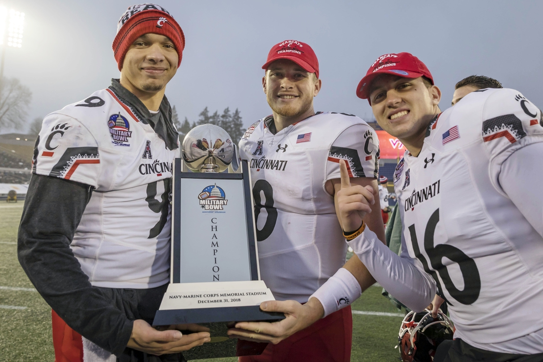 Dec 31, 2018; Annapolis, MD, USA; Cincinnati Bearcats quarterback Desmond Ridder (9) and quarterback Hayden Moore (8) and quarterback John Keller (16) pose with the Military Bowl Championship trophy after the game against the Virginia Tech Hokies at Navy-Marine Corps Memorial Stadium. Mandatory Credit: Scott Taetsch-USA TODAY Sports