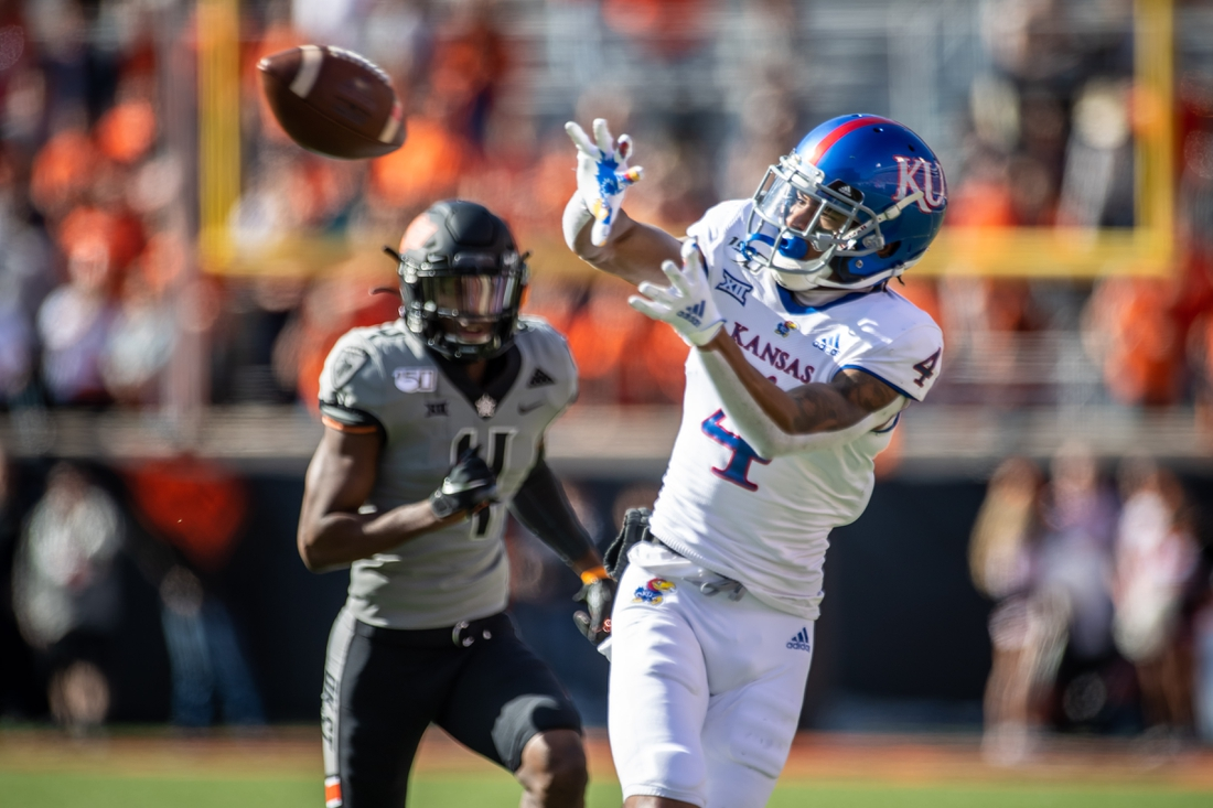 Nov 16, 2019; Stillwater, OK, USA; Kansas Jayhawks wide receiver Andrew Parchment (4) makes a catch while defended by Oklahoma State Cowboys cornerback A.J. Green (4) during the first half at Boone Pickens Stadium. Mandatory Credit: Rob Ferguson-USA TODAY Sports