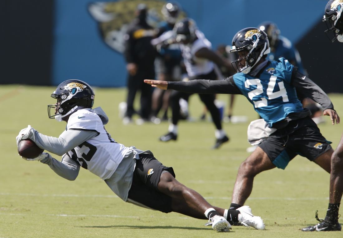 Aug 16, 2020; Jacksonville, Florida, United States;  Jacksonville Jaguars wide receiver Marvelle Ross (83) dives for a pass as corner back Josiah Scott (24) defends defends during training camp drills at the Dream Finders Homes training facility. Mandatory Credit: Reinhold Matay-USA TODAY Sports