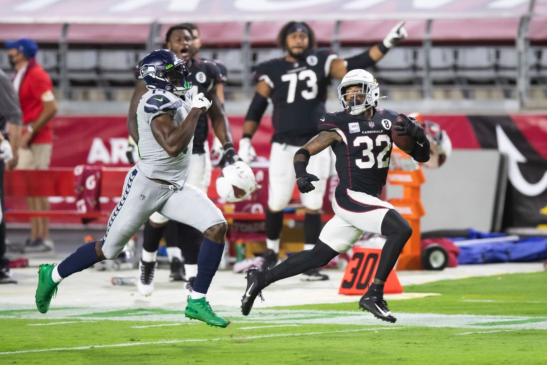 Oct 25, 2020; Glendale, Arizona, USA; Arizona Cardinals strong safety Budda Baker (32) runs the ball 90 yards against Seattle Seahawks wide receiver DK Metcalf (14) after catching an interception in the second quarter at State Farm Stadium. Mandatory Credit: Billy Hardiman-USA TODAY Sports