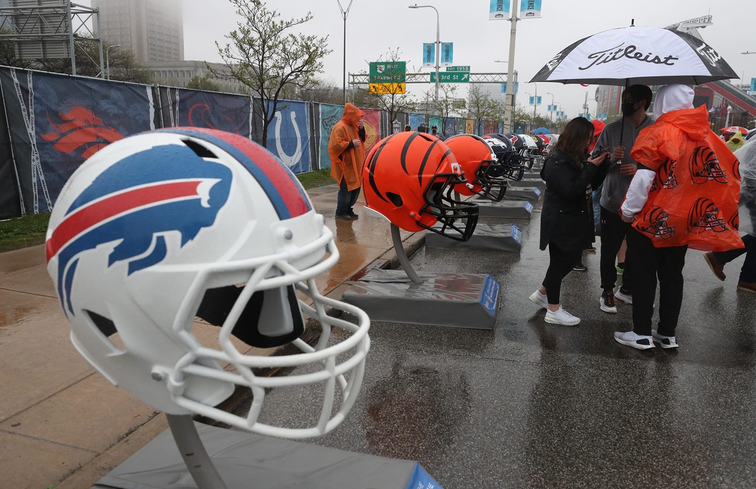 Fans try to stay dry as they check out the oversized team helmets at the NFL Draft Experience on Thursday April 29, 2021.  Draft 7