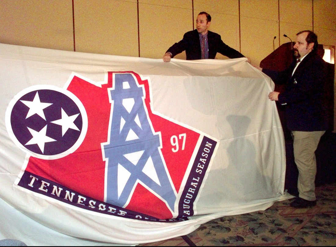 David Goldman, of NFL properties, left, and Alan Reitano drape a banner with the new Tennessee Oilers logo over a table before it is unveiled in Nashville June 12, 1997. The banner was placed over the table after it fell down from the wall. The Oilers will use the new logo during their inaugural season in Tennessee this year.  Houston Oilers