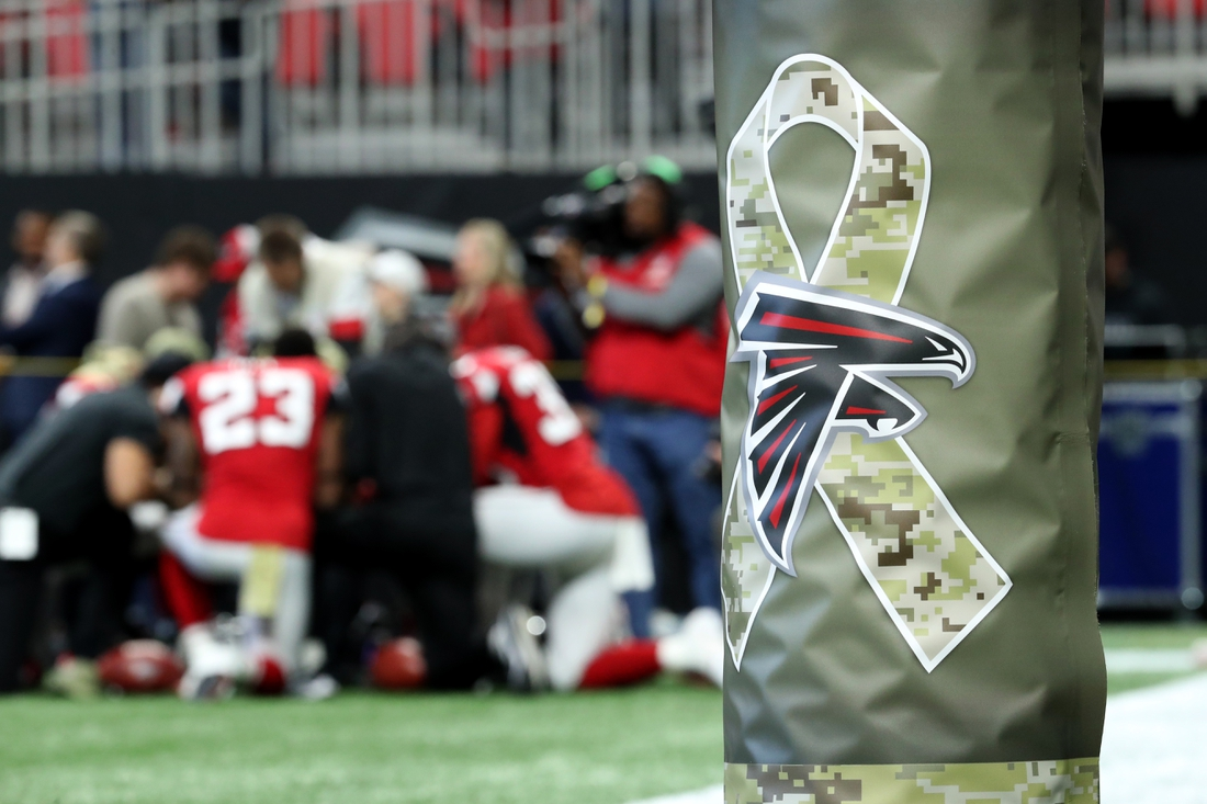Nov 24, 2019; Atlanta, GA, USA; The Atlanta Falcons logo is shown with a camouflage ribbon on a goalpost as the Atlanta Falcons running backs pray together before their game against the Tampa Bay Buccaneers at Mercedes-Benz Stadium. Mandatory Credit: Jason Getz-USA TODAY Sports