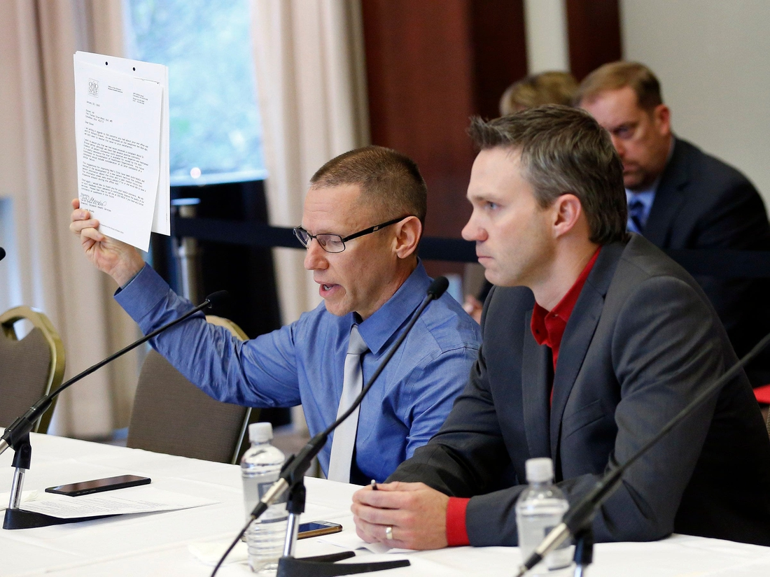 Victims of Dr. Richard Strauss, Brian Garrett, right, listens as Stephen Snyder Hill holds a document from Student Health Services while testifying to the extent of their abuse during an Ohio State University Board of Trustees meeting at the Longaberger Alumni House on Nov. 16, 2018.  Mt Trustees Ac 10