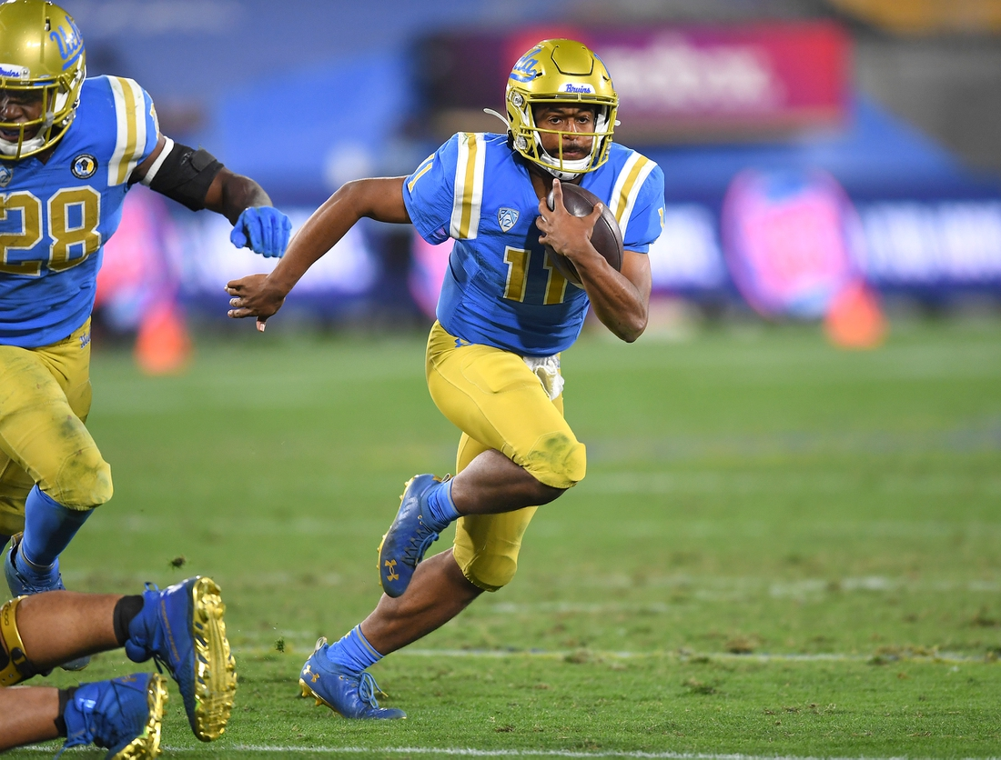 Dec 19, 2020; Pasadena, California, USA; UCLA Bruins quarterback Chase Griffin (11) runs the ball during overtime against the Stanford Cardinal at the Rose Bowl. Mandatory Credit: Jayne Kamin-Oncea-USA TODAY Sports