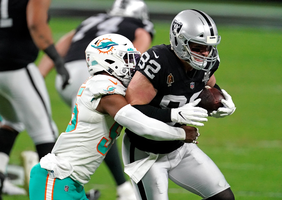 Dec 26, 2020; Paradise, Nevada, USA; Miami Dolphins outside linebacker Jerome Baker (55) tackles Las Vegas Raiders tight end Jason Witten (82) during the first half at Allegiant Stadium. Mandatory Credit: Kirby Lee-USA TODAY Sports