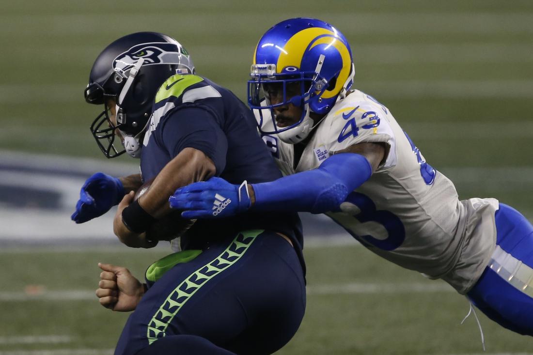 Jan 9, 2021; Seattle, Washington, USA; Los Angeles Rams safety John Johnson III (43) tackles Seattle Seahawks quarterback Russell Wilson (3) during the fourth quarter at Lumen Field. Mandatory Credit: Joe Nicholson-USA TODAY Sports