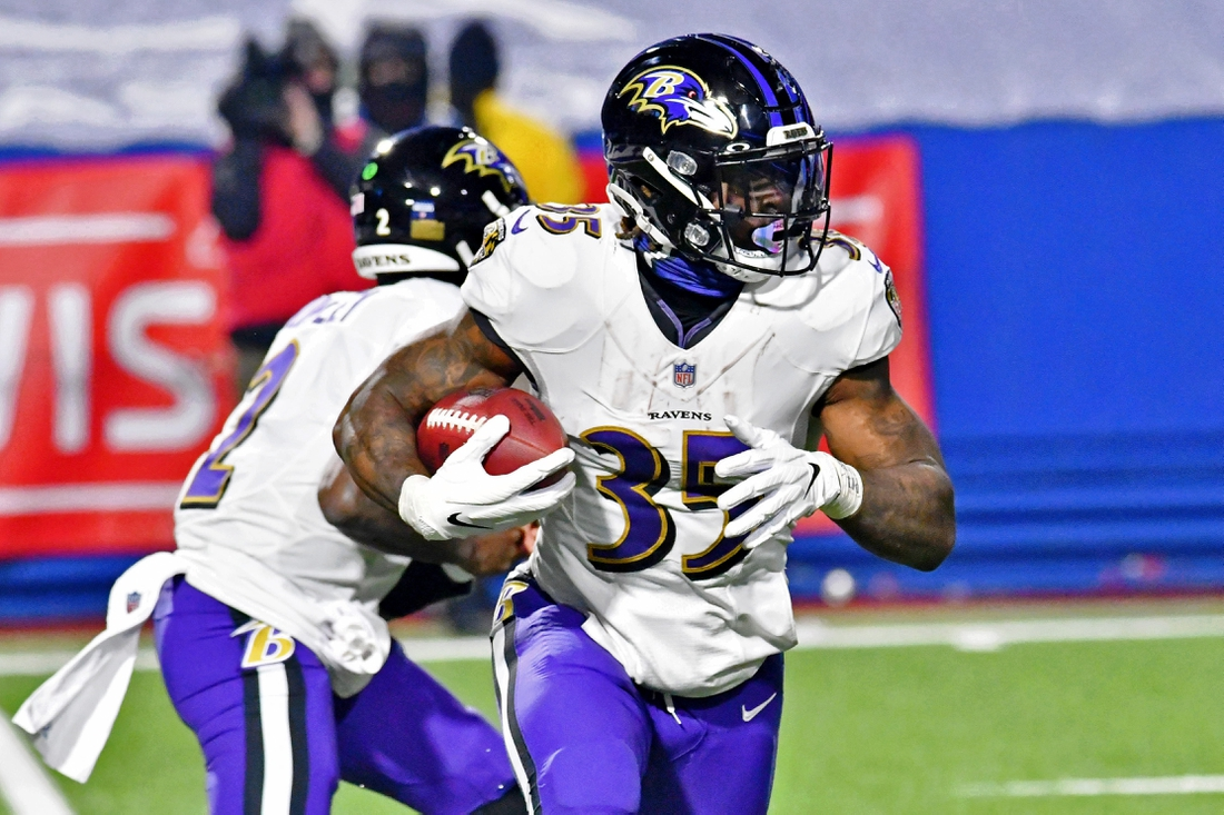 Jan 16, 2021; Orchard Park, New York, USA; Baltimore Ravens running back Gus Edwards (35) runs with the ball against the Buffalo Bills during the second half of an AFC Divisional Round playoff game at Bills Stadium. The Buffalo Bills won 17-3. Mandatory Credit: Mark Konezny-USA TODAY Sports