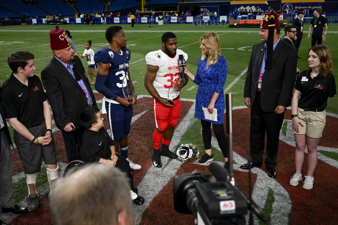 Jan 18, 2020; St. Petersburg, Florida, USA; Team East running back Benny LeMay (32) and Team West safety Luther Kirk (34) receive the trophy for defensive and offensive most valuable player respectively in the 95th East-West Shrine Bowl at Tropicana Field. Mandatory Credit: Douglas DeFelice-USA TODAY Sports