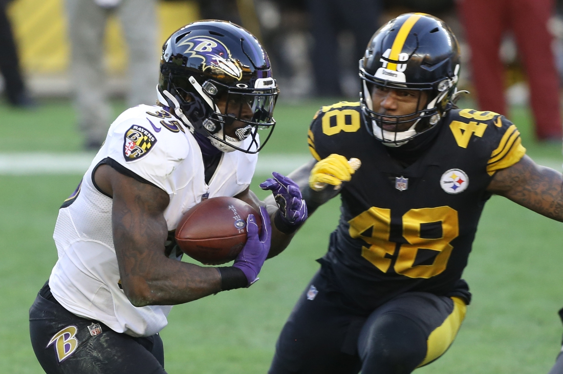 Dec 2, 2020; Pittsburgh, Pennsylvania, USA;  Baltimore Ravens running back Gus Edwards (35) carries the ball against Pittsburgh Steelers outside linebacker Bud Dupree (48) during the first quarter at Heinz Field. Mandatory Credit: Charles LeClaire-USA TODAY Sports