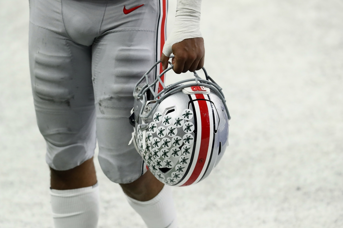Dec 19, 2020; Indianapolis, Indiana, USA; A member of the Ohio State Buckeyes carries his helmet off the field after defeating the Northwestern Wildcats at Lucas Oil Stadium. Mandatory Credit: Aaron Doster-USA TODAY Sports
