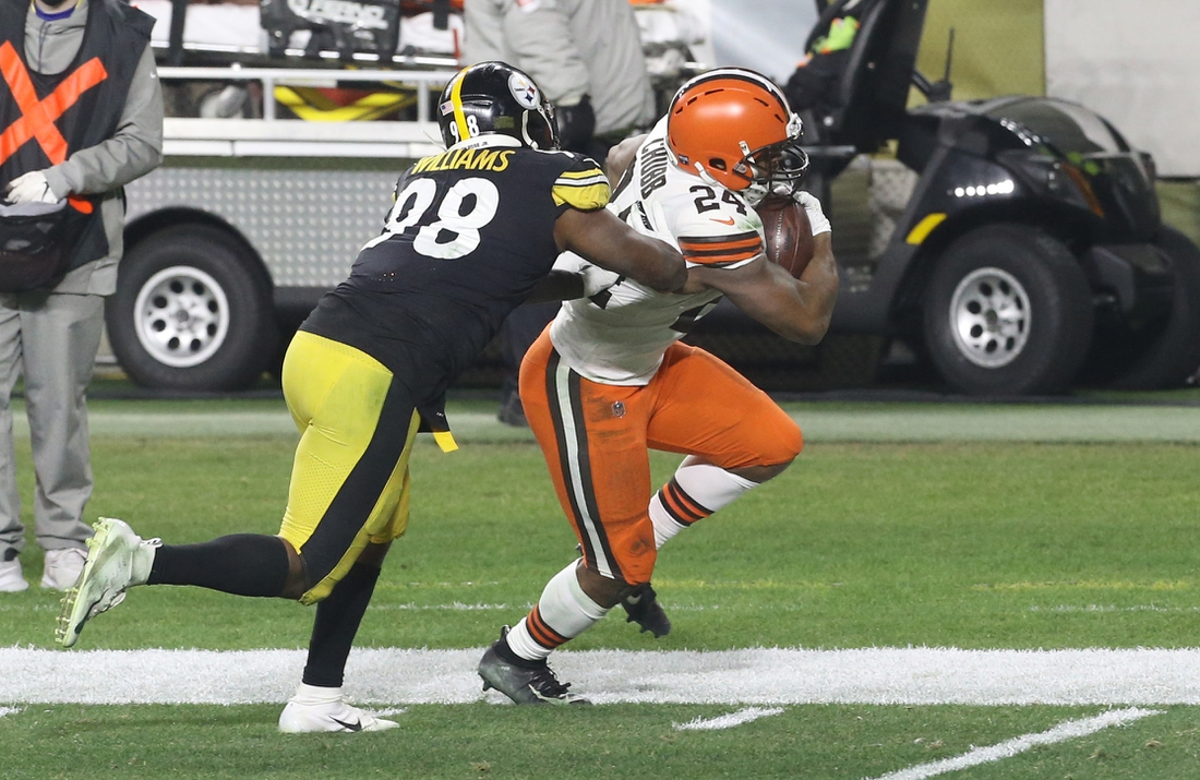 Jan 10, 2021; Pittsburgh, Pennsylvania, USA;  Cleveland Browns running back Nick Chubb (24) runs the ball against Pittsburgh Steelers inside linebacker Vince Williams (98) during the first quarter at Heinz Field. The Browns won 48-37. Mandatory Credit: Charles LeClaire-USA TODAY Sports