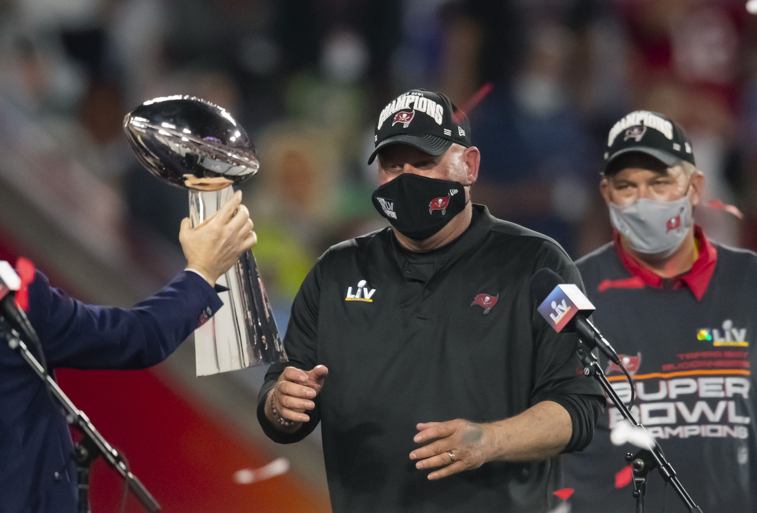 Feb 7, 2021; Tampa, FL, USA;  Tampa Bay Buccaneers head coach Bruce Arians is handed the Vince Lombardi Trophy after the Tampa Bay Buccaneers beat the Kansas City Chiefs in Super Bowl LV at Raymond James Stadium.  Mandatory Credit: Mark J. Rebilas-USA TODAY Sports