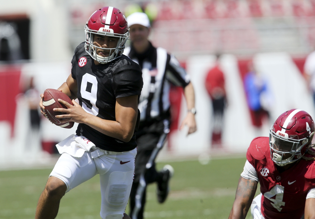 Apr 17, 2021; Tuscaloosa, Alabama, USA; White quarterback Bryce Young (9) scrambles for a first down after moving away from Crimson linebacker Christopher Allen (4) during the Alabama A-Day game at Bryant-Denny Stadium. Mandatory Credit: Gary Cosby-USA TODAY Sports