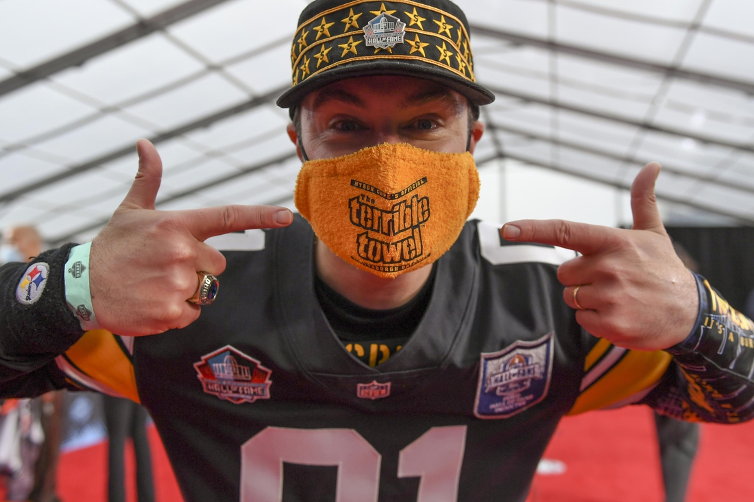 Apr 29, 2021; Cleveland, OH, USA; Rick Dermer, a fan of the Pittsburgh Steelers, points out his Terrible Towel Mask as he waits for potential draftees to appear on the Red Carpet at the Rock & Roll Hall of Fame before the first round of the 2021 NFL football draft, Thursday, April 29, 2021, in Cleveland.  Mandatory Credit: David Dermer/Pool Photo-USA TODAY Sports