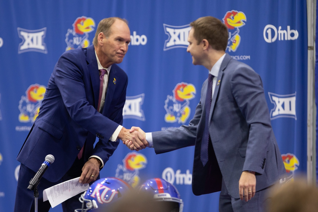 The University of Kansas new football coach Lance Leipold, left, shakes hands with athletic director Travis Goff, right, during a news conference Monday at the indoor football facility.
