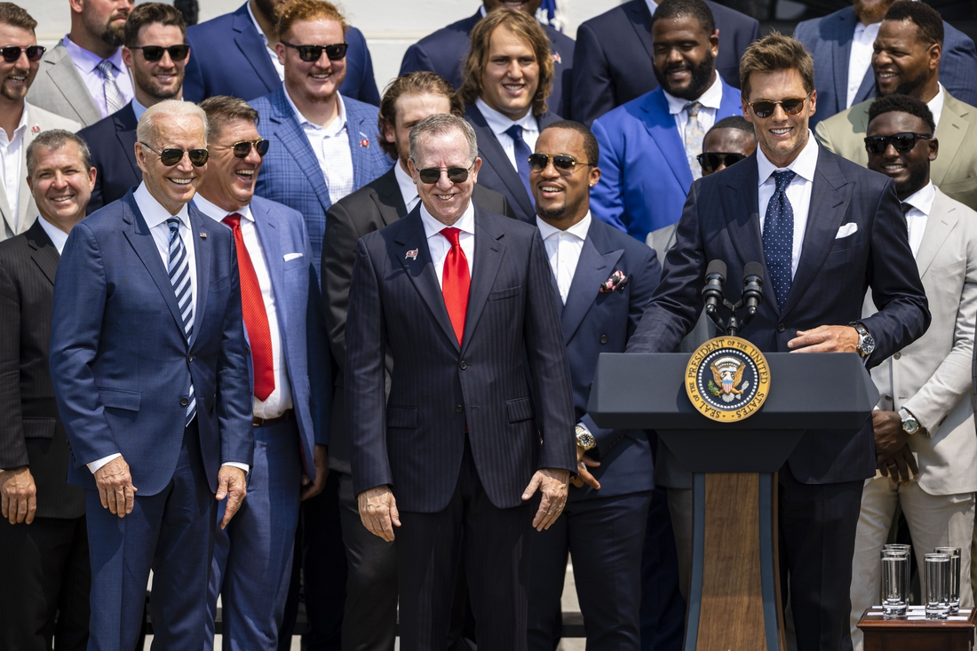 Jul 20, 2021; Washington, DC, USA; Tampa Bay Buccaneers quarterback Tom Brady speaks at the podium as President Joe Biden (left) and Buccaneers owner Bryan Glazer (middle) react during a ceremony on the South Lawn of the White House to honor the team for their Super Bowl LV Championship. Mandatory Credit: Scott Taetsch-USA TODAY Sports