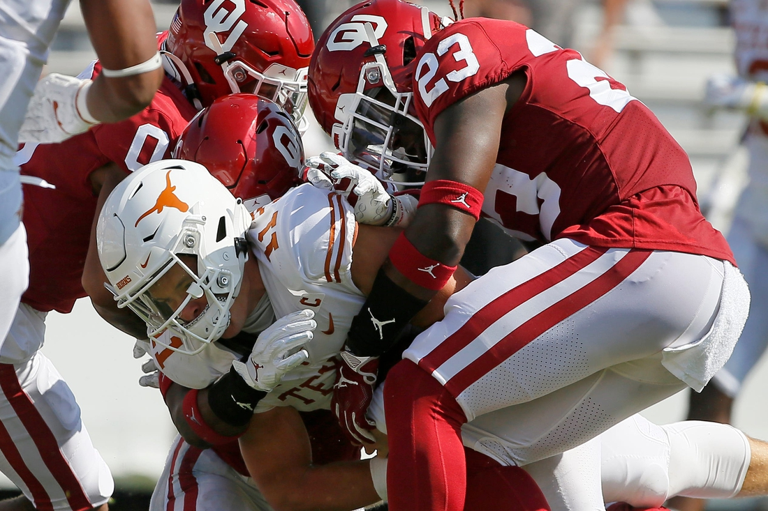 OU's DaShaun White (23) and Delarrin Turner-Yell (32) bring down Texas quarterback Sam Ehlinger (11) during the Sooners' 53-45 win in Dallas on Oct. 10, 2020.  ehlinger