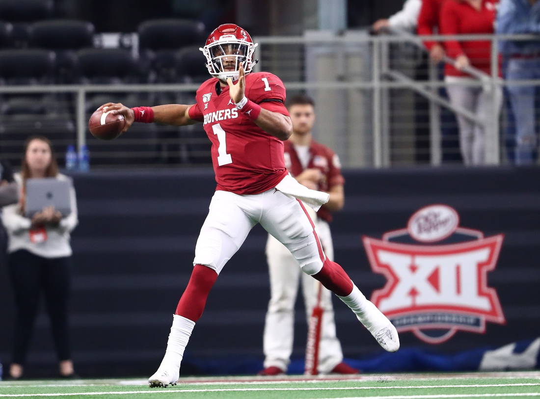 Dec 7, 2019; Arlington, TX, USA; Oklahoma Sooner quarterback Jalen Hurts (1) scrambles in front of the Big 12 logo during the second half against the Baylor Bears in the 2019 Big 12 Championship Game at AT&T Stadium. Mandatory Credit: Matthew Emmons-USA TODAY Sports