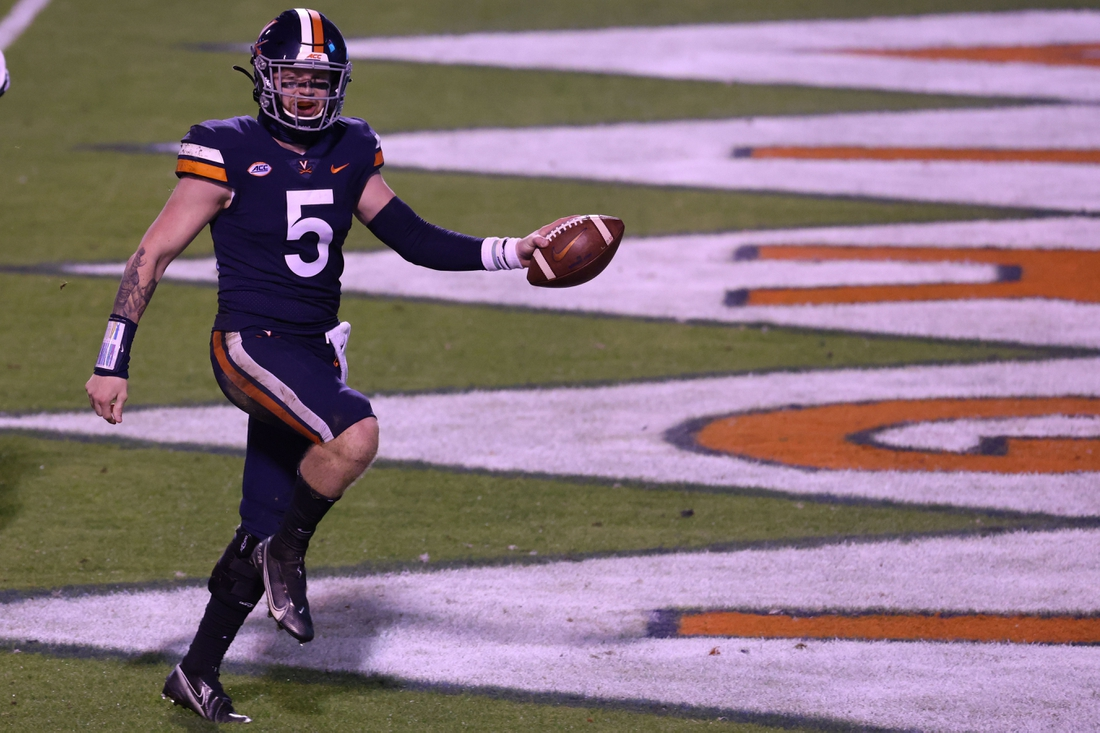 Nov 14, 2020; Charlottesville, Virginia, USA; Virginia Cavaliers quarterback Brennan Armstrong (5) celebrates after scoring a touchdown against the Louisville Cardinals in the fourth quarter at Scott Stadium. Mandatory Credit: Geoff Burke-USA TODAY Sports