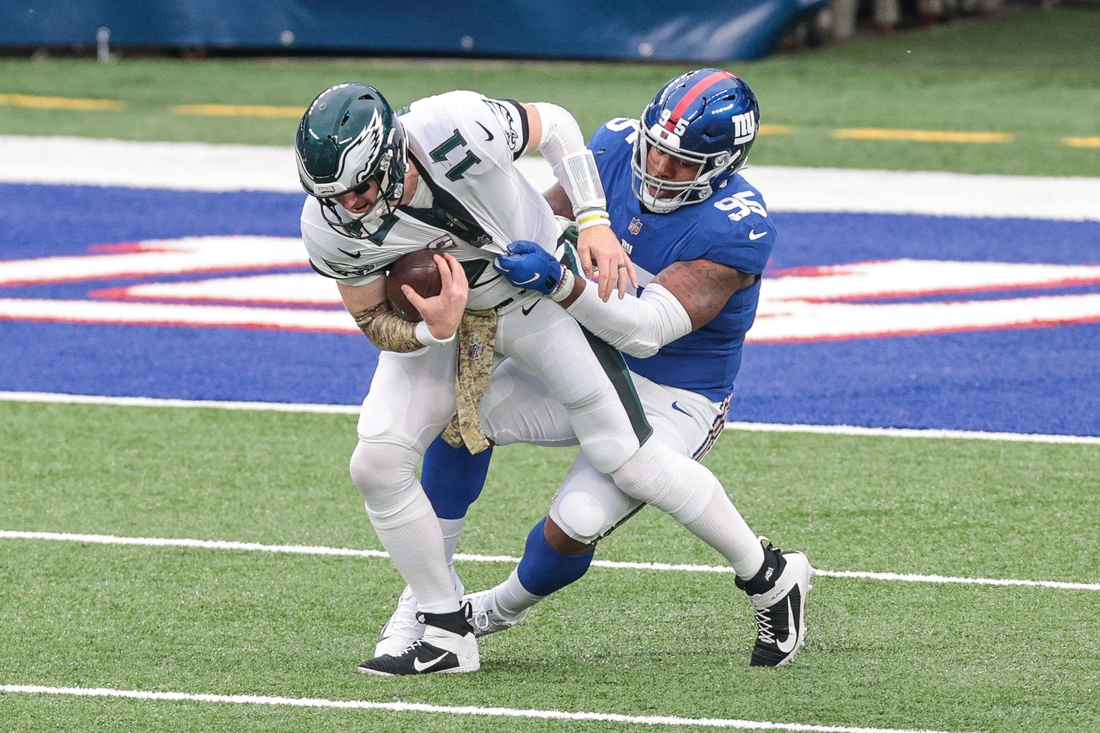 Nov 15, 2020; East Rutherford, New Jersey, USA; Philadelphia Eagles quarterback Carson Wentz (11) is sacked by New York Giants defensive tackle B.J. Hill (95) during the first half at MetLife Stadium. Mandatory Credit: Vincent Carchietta-USA TODAY Sports
