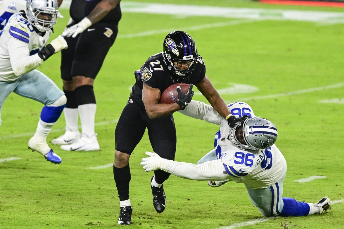 Dec 8, 2020; Baltimore, Maryland, USA; Baltimore Ravens running back J.K. Dobbins (27) stiff arms Dallas Cowboys defensive tackle Neville Gallimore (96) during the second half  at M&T Bank Stadium. Mandatory Credit: Tommy Gilligan-USA TODAY Sports