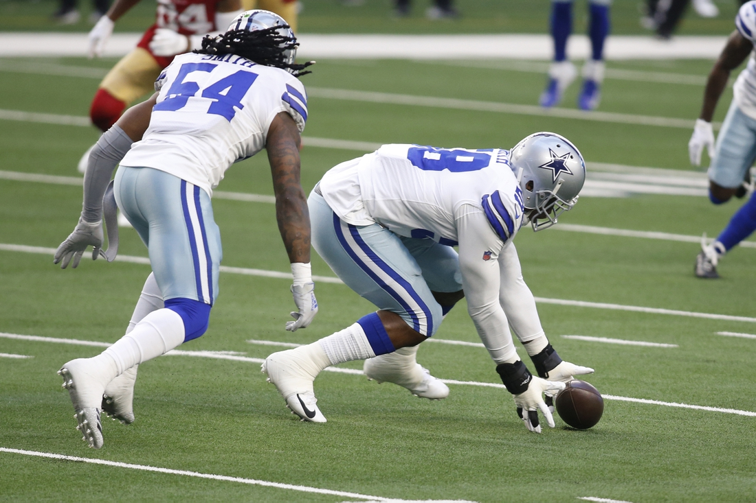 Dec 20, 2020; Arlington, Texas, USA; Dallas Cowboys defensive end Aldon Smith (58) picks up a fumble against the San Francisco 49ers in the first quarter at AT&T Stadium. Mandatory Credit: Tim Heitman-USA TODAY Sports