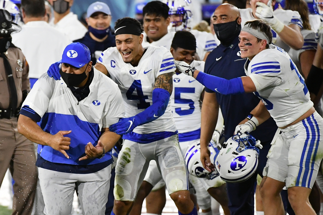 Dec 22, 2020; Boca Raton, Florida, USA; Brigham Young Cougars head coach Kalani Sitake celebrates with defensive back Troy Warner (4) after defeating the UCF Knights at FAU Stadium. Mandatory Credit: Jasen Vinlove-USA TODAY Sports