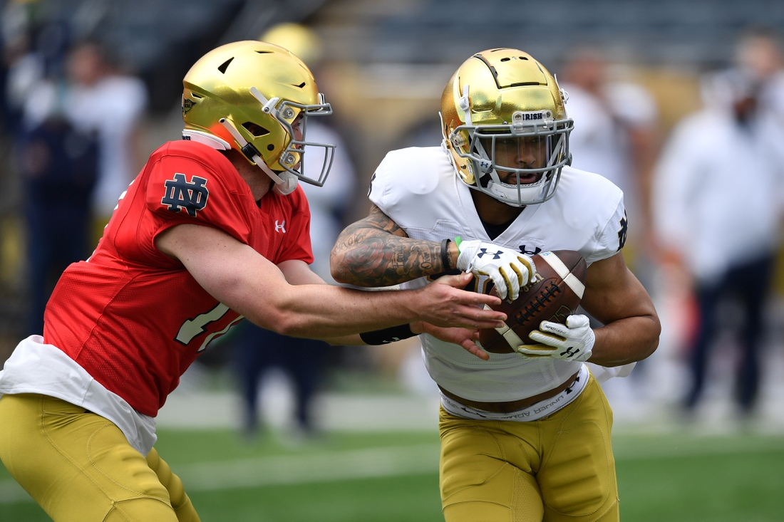 May 1, 2021; Notre Dame, Indiana, USA; Notre Dame Fighting Irish quarterback Jack Coan (17) hands off to running back Kyren Williams (23) in the first quarter of the Blue-Gold Game at Notre Dame Stadium. Mandatory Credit: Matt Cashore-USA TODAY Sports