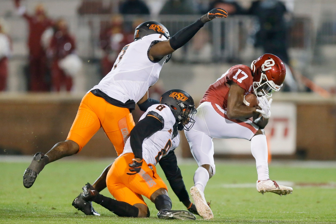 Oklahoma's Marvin Mims (17) catches the ball in front of Oklahoma State's Amen Ogbongbemiga (7) and Rodarius Williams (8) during a Bedlam college football game between the University of Oklahoma Sooners (OU) and the Oklahoma State Cowboys (OSU) at Gaylord Family-Oklahoma Memorial Stadium in Norman, Okla., Saturday, Nov. 21, 2020. Oklahoma won 41-13. [Bryan Terry/The Oklahoman]  Photo 5