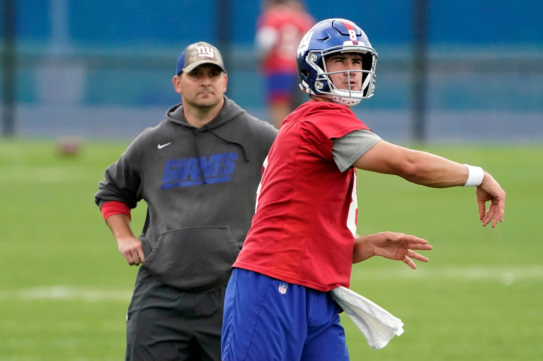 New York Giants quarterback Daniel Jones (8) throws the ball as head coach Joe Judge looks on during OTA practice at the Quest Diagnostics Training Center on Friday, June 4, 2021, in East Rutherford.  Giants Ota Practice