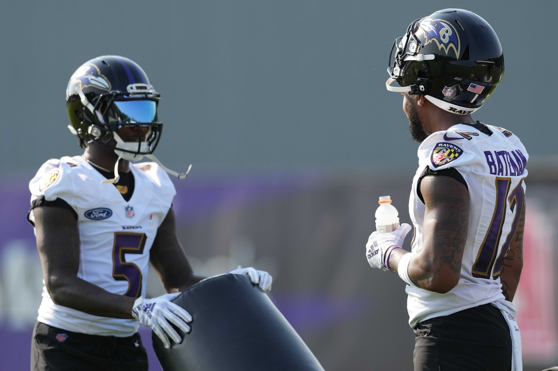 Jul 28, 2021; Owings Mills, MD, United States; Baltimore Ravens wide receivers Rashod Bateman (12) and Marquise Brown (5) talk during a break at Under Armour Performance Center. Mandatory Credit: Mitch Stringer-USA TODAY Sports