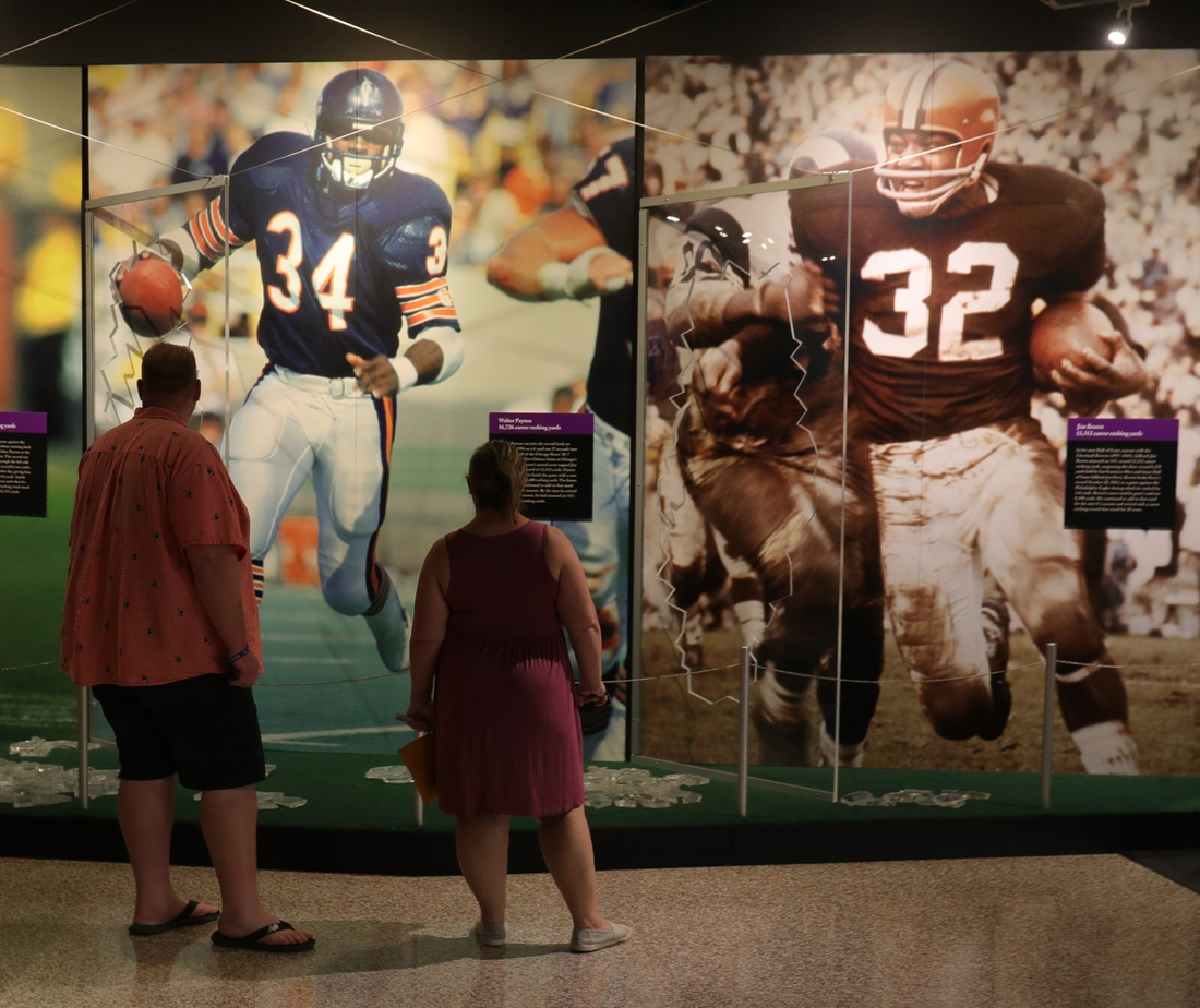 Fans look at the photo display in the HOF museum the Pro Football Hall of Fame Enshrinement ceremony Sunday, Aug. 8, 2021 at Tom Benson Hall of Fame Stadium in Canton, Ohio.  Hof Calvin