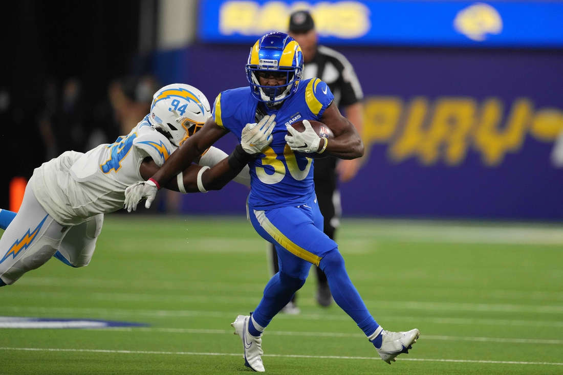 Aug 14, 2021; Inglewood, California, USA; Los Angeles Rams running back Raymond Calais (30) runs the ball against Los Angeles Chargers linebacker Chris Rumph (94) in the second half at SoFi Stadium. Mandatory Credit: Kirby Lee-USA TODAY Sports