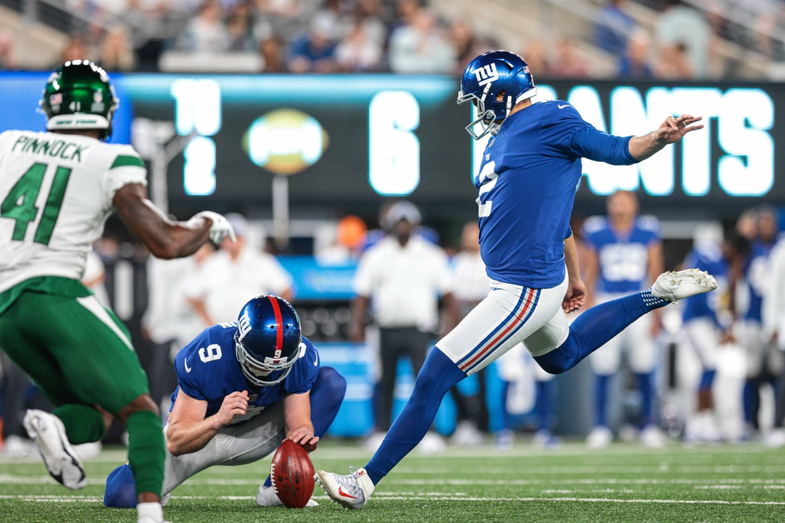 Aug 14, 2021; East Rutherford, New Jersey, USA;  New York Giants punter Ryan Santoso (2) kicks an extra point as New York Giants punter Riley Dixon (9) holds and New York Jets cornerback Jason Pinnock (41) defends during the second half at MetLife Stadium. Mandatory Credit: Vincent Carchietta-USA TODAY Sports
