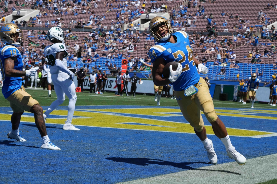 Aug 28, 2021; Pasadena, California, USA;  UCLA Bruins running back Zach Charbonnet (24) scores on a 21-yard touchdown run in the second quarter against the Hawaii Rainbow Warriors at Rose Bowl. Mandatory Credit: Kirby Lee-USA TODAY Sports