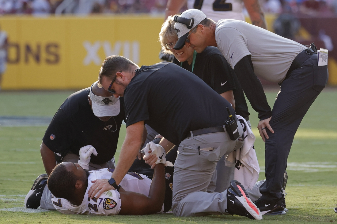 Aug 28, 2021; Landover, Maryland, USA; Baltimore Ravens head coach John Harbaugh (R) looks on as team medical personnel help Ravens running back J.K. Dobbins (27) after being injured against the Washington Football Team in the first quarter at FedExField. Mandatory Credit: Geoff Burke-USA TODAY Sports