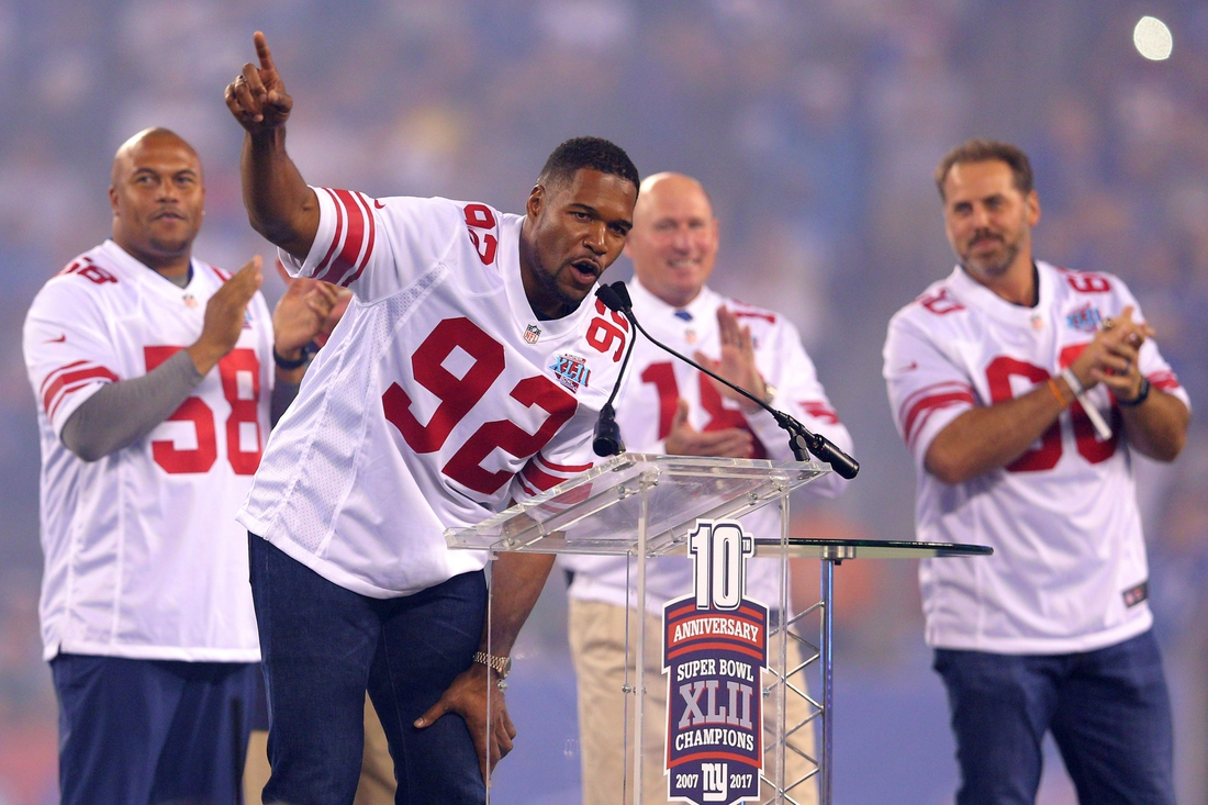 Sep 18, 2017; East Rutherford, NJ, USA; Former New York Giants player Michael Strahan speaks in front of former players Antonio Pierce (58) and Jeff Feagles (18) and Shaun O'Hara (60) during a halftime ceremony honoring the 2007 Super Bowl champion Giants during a game against the Detroit Lions at MetLife Stadium. Mandatory Credit: Brad Penner-USA TODAY Sports