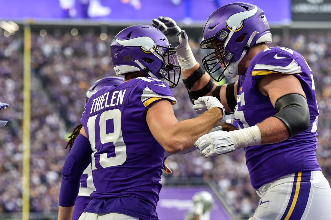 Sep 22, 2019; Minneapolis, MN, USA; Minnesota Vikings wide receiver Adam Thielen (19) reacts with offensive tackle Brian O'Neill (75) after catching a 35 yard touchdown pass from quarterback Kirk Cousins (not shown) against the Oakland Raiders during the first quarter at U.S. Bank Stadium. Mandatory Credit: Jeffrey Becker-USA TODAY Sports