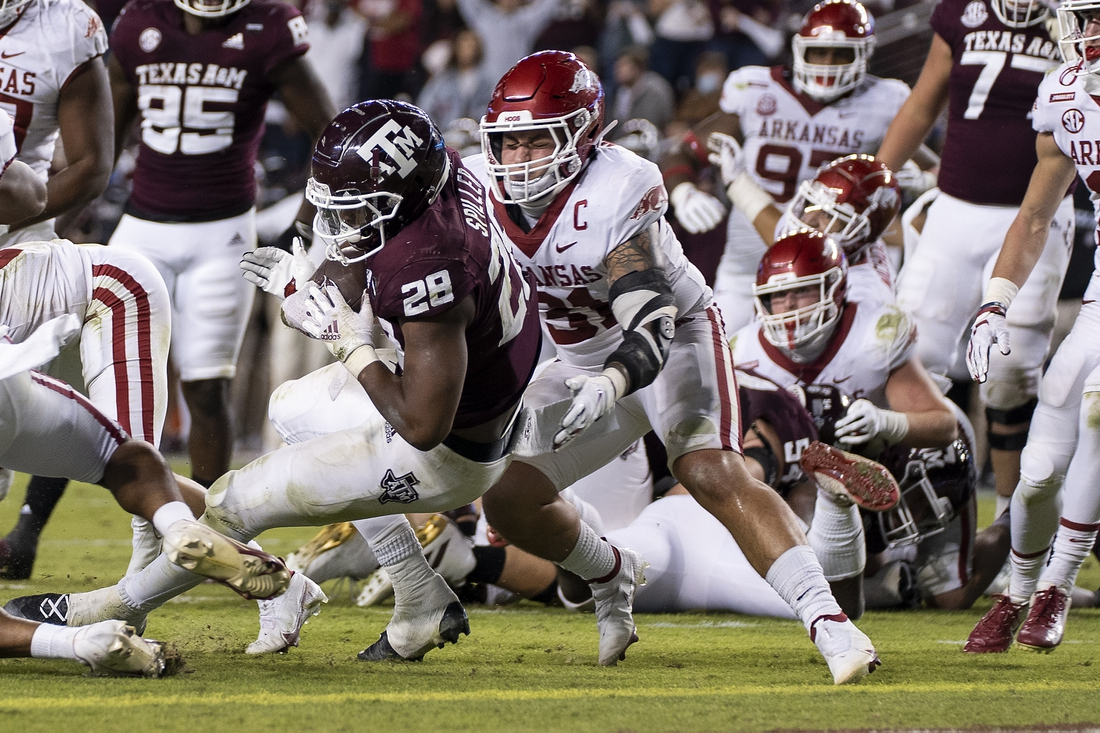 Oct 31, 2020; College Station, TX, USA; Texas A&M running back Isaiah Spiller (28) rushes for a touchdown against Arkansas linebacker Grant Morgan (31) during the second quarter of an NCAA college football game, Saturday, Oct. 31, 2020, in College Station, Texas. Mandatory Credit: Sam Craft/Pool Photo-USA TODAY Sports