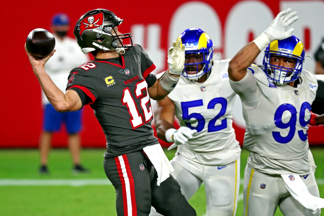 Nov 23, 2020; Tampa, Florida, USA;  Tampa Bay Buccaneers quarterback Tom Brady (12) throws a pass against Los Angeles Rams defensive end Aaron Donald (99) during the first quarter at Raymond James Stadium. Mandatory Credit: Kim Klement-USA TODAY Sports