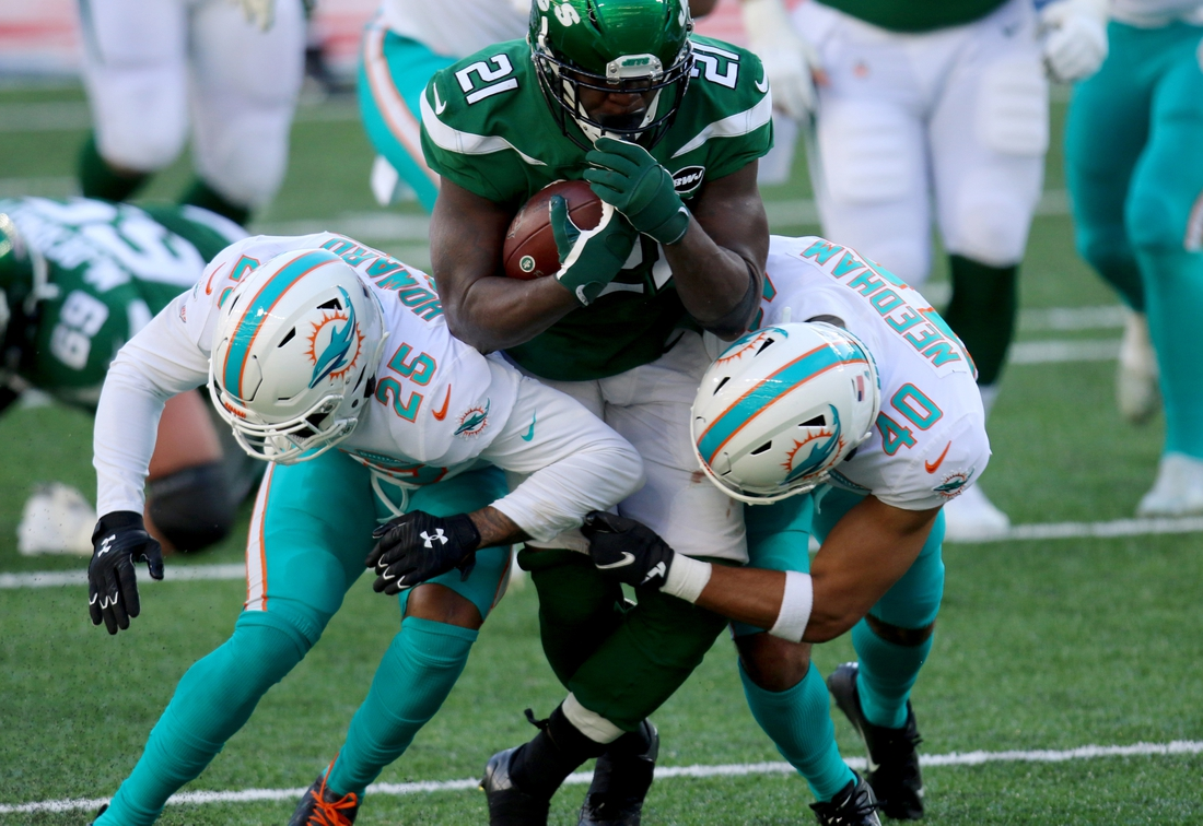 Nov 29, 2020; East Rutherford, New Jersey, USA; New York Jets running back Frank Gore (21) runs against Miami Dolphins cornerback Xavien Howard (25) and defensive back Nik Needham (40) during the first half at MetLife Stadium. Mandatory Credit: Kevin Wexler-USA TODAY Sports