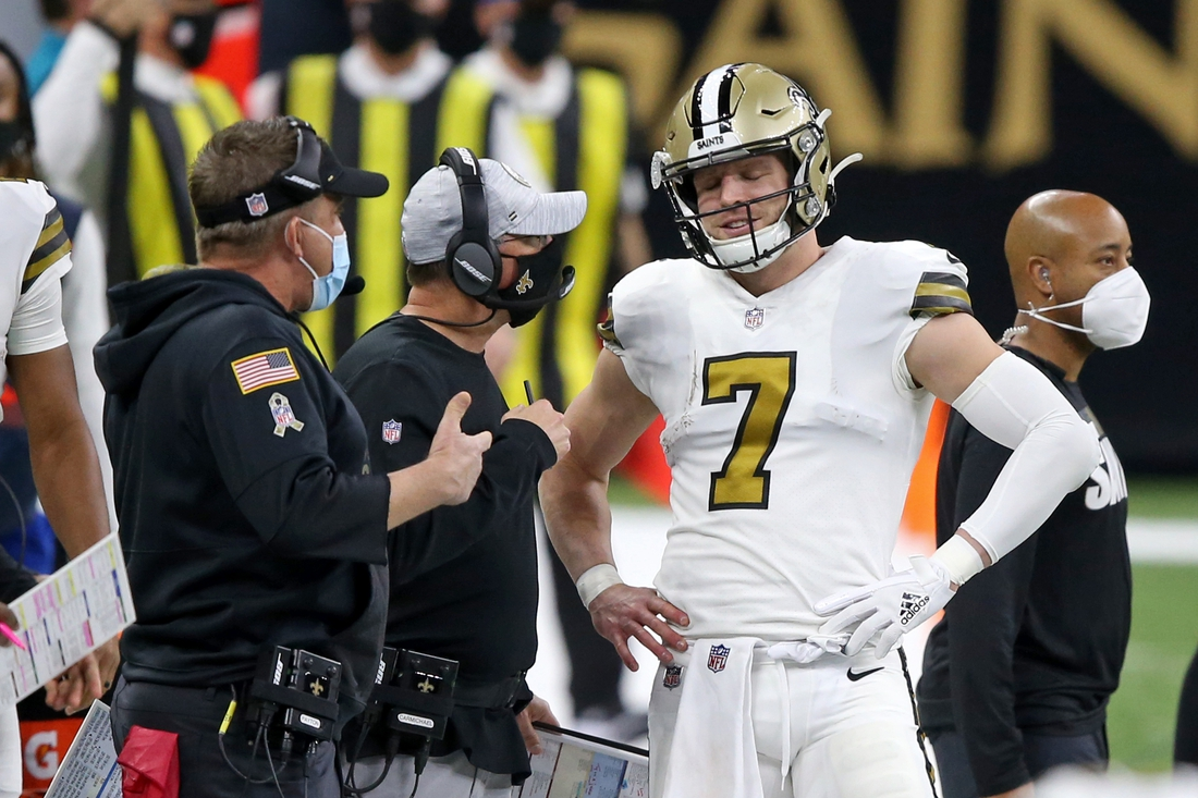 Dec 25, 2020; New Orleans, Louisiana, USA; New Orleans Saints quarterback Taysom Hill (7) talks to head coach Sean Payton and offensive coordinator Pete Carmichael in the second quarter at the Mercedes-Benz Superdome. Mandatory Credit: Chuck Cook-USA TODAY Sports