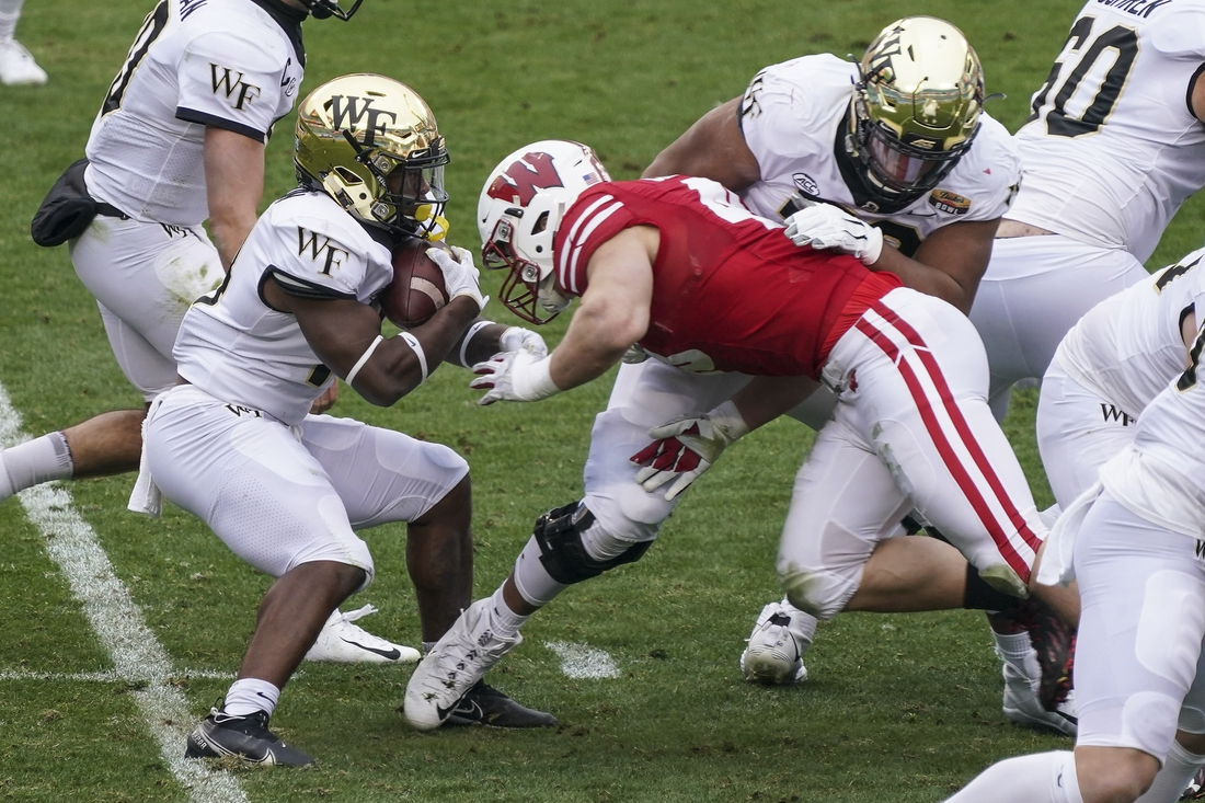 Dec 30, 2020; Charlotte, NC, USA; Wake Forest Demon Deacons running back Justice Ellison (14) is tackled for a loss of yardage by Wisconsin Badgers linebacker Leo Chenal (45) during second quarter action at Bank of America Stadium. Mandatory Credit: Jim Dedmon-USA TODAY Sports
