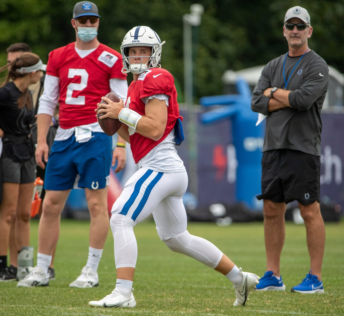 Indianapolis Colts quarterback Sam Ehlinger (4) drops back to pass as he is watched by Carson Wentz and Indianapolis Colts head coach Frank Reich during a combined Indianapolis Colts and Carolina Panthers practice at Grand Park in Westfield on Thursday, August 12, 2021, during Colts camp.  Colts Entertain Panthers