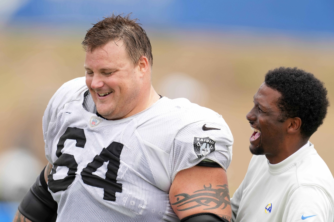 Aug 18, 2021; Thousand Oaks, CA, USA; Las Vegas Raiders  guard Richie Incognito (64) interacts with Los Angeles Rams vice president of communications Artis Twyman during a joint practice. Mandatory Credit: Kirby Lee-USA TODAY Sports