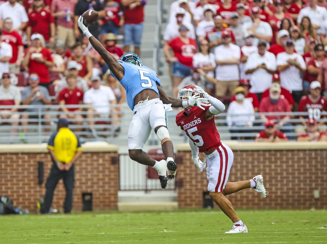 Sep 4, 2021; Norman, Oklahoma, USA;  Tulane Green Wave running back Ygenio Booker (5) makes a leaping catch in front of Oklahoma Sooners defensive back Billy Bowman (5) during the first quarter at Gaylord Family-Oklahoma Memorial Stadium. Mandatory Credit: Kevin Jairaj-USA TODAY Sports