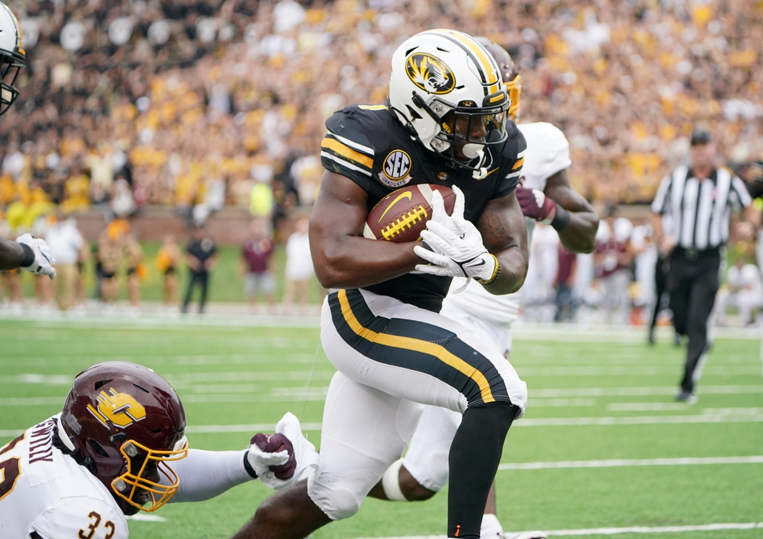 Sep 4, 2021; Columbia, Missouri, USA; Missouri Tigers running back Tyler Badie (1) scores a touchdown as Central Michigan Chippewas linebacker Nick Apsey (32) attempts the tackle during the first half at Faurot Field at Memorial Stadium. Mandatory Credit: Denny Medley-USA TODAY Sports